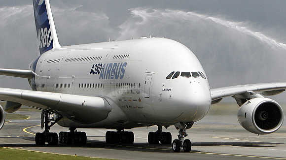 An Airbus A380 jet passes under the welcoming spray of firemen's hoses as it taxies on the runway after landing a