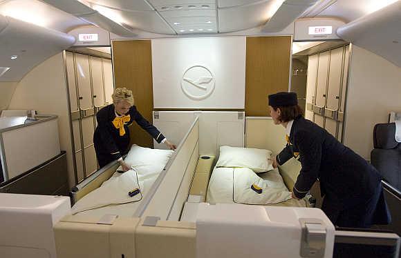 Flight attendants prepare beds of the First Class inside Lufthansa's A380 in Finkenwerder, near Hamburg, Germany.