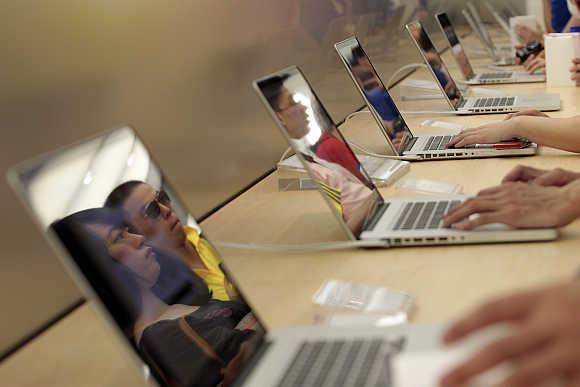 Customers check Apple laptops in Shanghai.