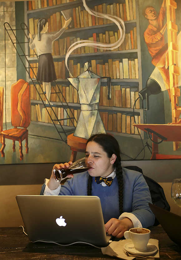 Nadine Maestas enjoys a beer after her coffee while studying at Starbucks' Roy Street Coffee and Tea in Seattle, Washington.