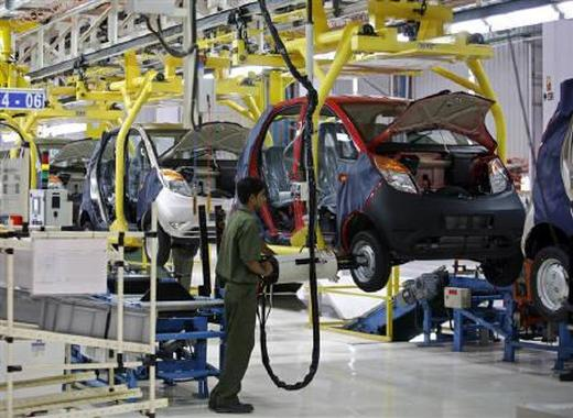 An employee works inside the plant for the Tata Nano car