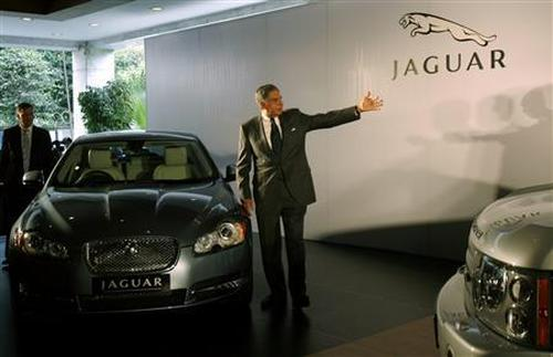 Tata Motors chairman Ratan Tata gestures as he stands next to a Jaguar XF during a launch of Jaguar and Land Rover in India