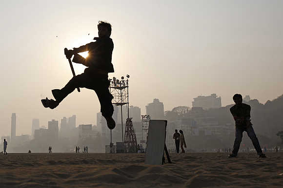 A man jumps in the air to hit a ball as people play cricket by the beach in Mumbai.