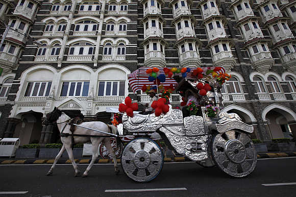 A horse-drawn carriage carrying tourists moves past the Taj Mahal hotel in Mumbai.