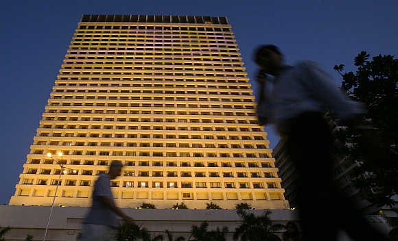 People walk past the lit-up Trident hotel in Mumbai.