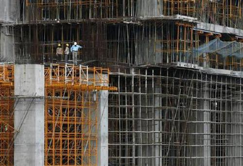 Workers stand at a construction site of a high rise building.