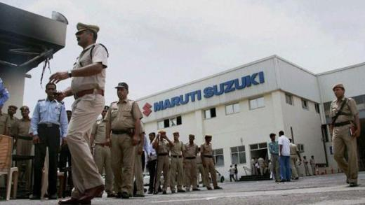 Police officials walk outside the Maruti Suzuki's plant in Manesar