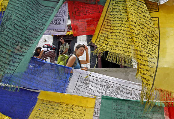 French tourist walks past Buddhist religious flags at Namgyal Tsemo Gompa monastery in Leh.