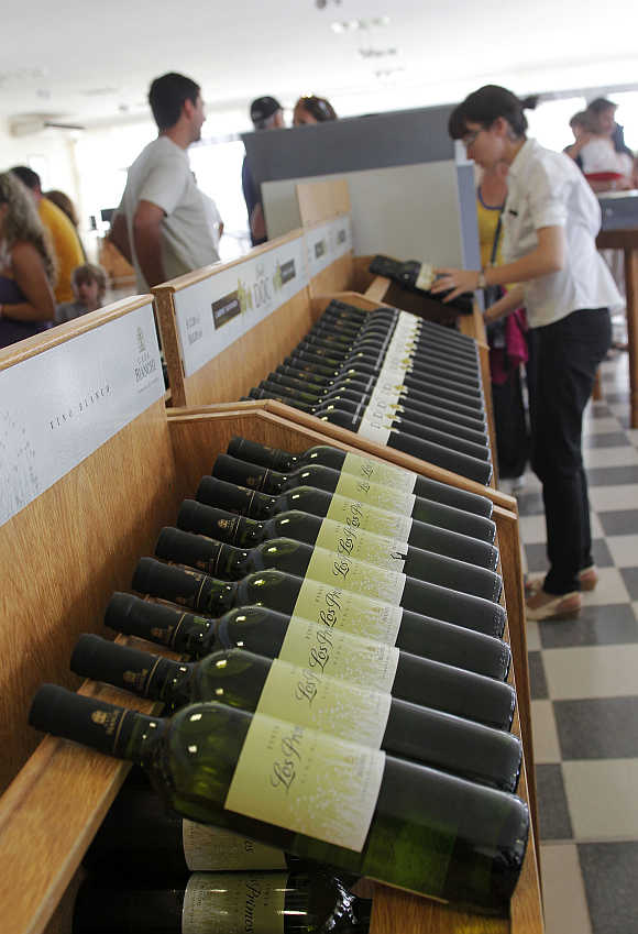 A wine expert places bottles of wine on display in a shop in Casa Bianchi in San Rafael, Argentina.
