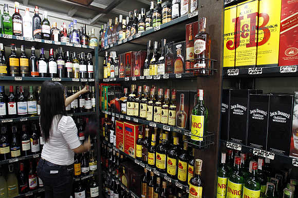 A saleslady cleans a display inside a wine shop in Manila, Philippines.