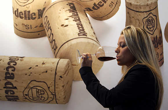 A woman tests a glass of red wine at the Vinitaly wine expo in Verona, Italy.