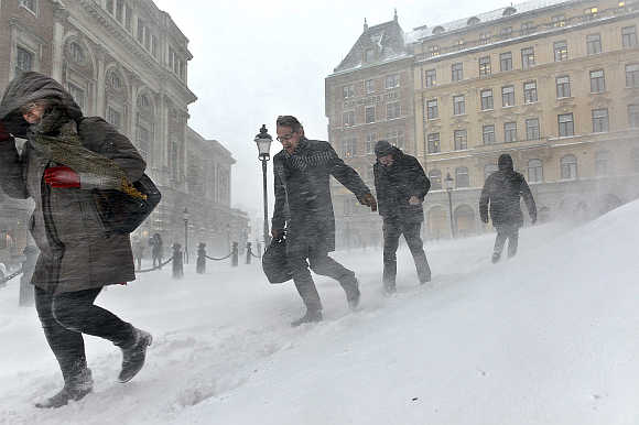 People struggle against wind and drifting snow in Stockholm, Sweden.