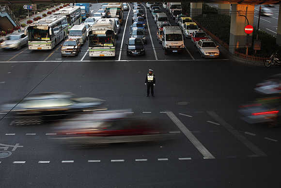 A policeman directs the traffic at a busy street of downtown Shanghai.
