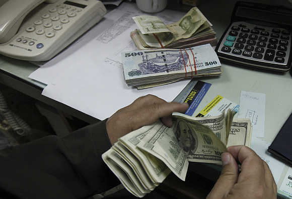 A currency exchange trader counts money in his office in Islamabad.