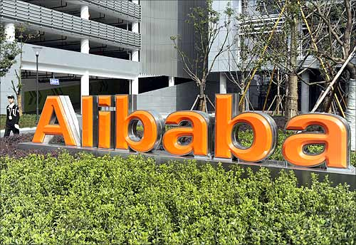 A security guard walks past a logo of Alibaba (China) Technology Co. Ltd at its headquarters on the outskirts of Hangzhou.