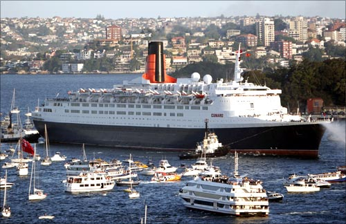 Queen Elizabeth 2 arrives in Sydney harbour, accompanied by a flotilla of small craft.
