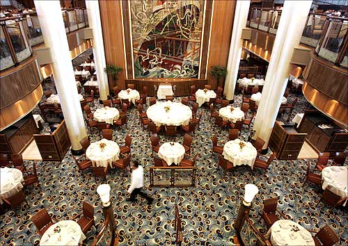 A waiter walks inside the Britannia Restaurant aboard the Queen Mary 2.
