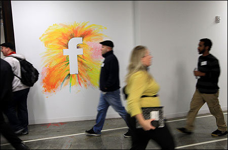 Employees walk past the company logo at the new headquarters of Facebook in Me