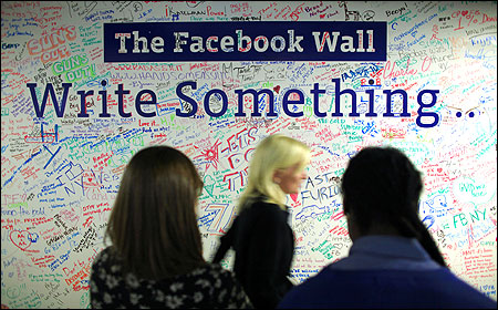 People walk past the Facebook wall inside their office in New York.