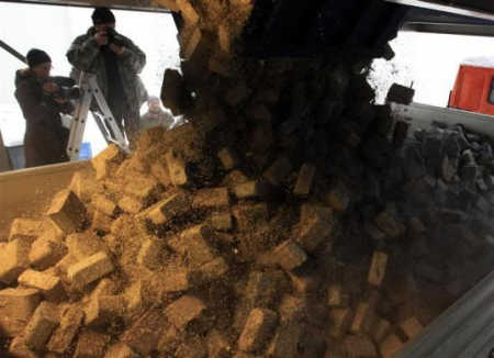 Four tonnes of shredded and compressed banknotes are loaded onto a truck.