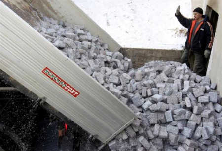 Tonnes of shredded and compressed banknotes are unloaded.