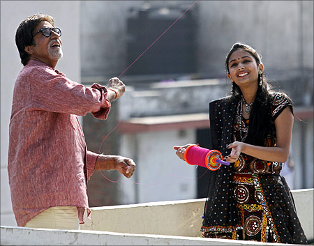Bollywood actor Amitabh Bachchan (left) flies a kite during a shoot for a movie to promote tourism in Gujarat.