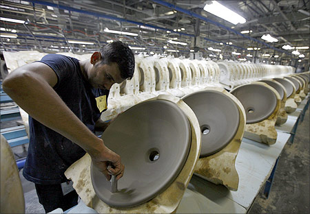 An employee works inside the Duravit production site, which produces wash basins and other toilet goods, at Tarapur.