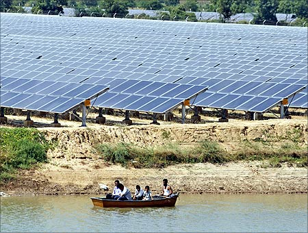 Security personnel sit in a boat as they patrol the premises of a newly inaugurated solar farm at Gunthawada village in Banaskantha district.