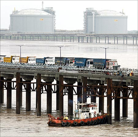 Pillars of the newly inaugurated cargo port are checked as trucks wait to load coal at Dahej.