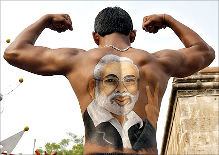 A devotee shows his back, with an image of Gujarat Chief Minister Narendra Modi, as he flexes his muscles.