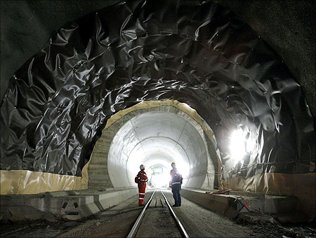A worker and a visitor stand at the construction site of the NEAT Gotthard Base Tunnel at the Erstfeld-Ams