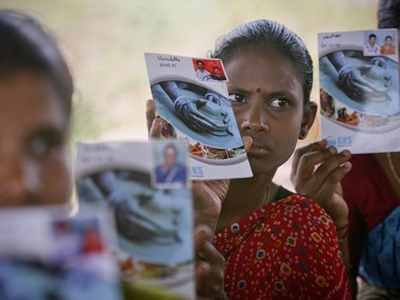 Loan borrowers show pass books given to them by a micro finance company