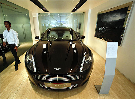 An employee walks past an Aston Martin Rapide inside the company's showroom in Mumbai.