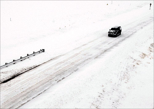 A truck travels along Highway 40 as snow covers the highway and the surrounding plains, west of Hays, Kansas.