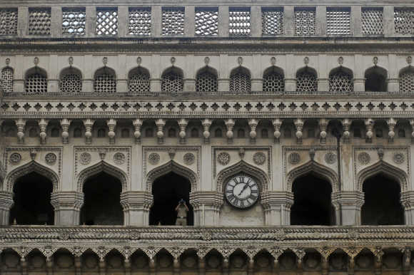 A security personnel watches through a pair of binoculars from the historical monument Charminar in Hyderabad.