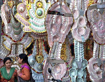 Women stand next to a shop selling garlands made of Indian currency notes.