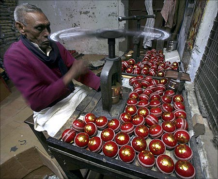 A worker stamps balls before they are packed at a factory in Meerut.