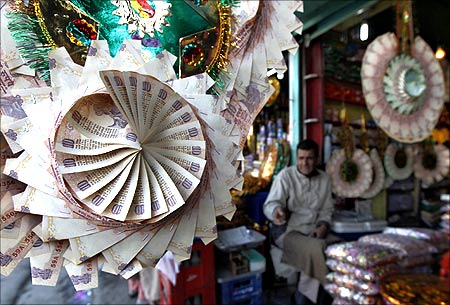 A Kashmiri shopkeeper sits near garlands made of Indian currency notes at a market in Srinagar