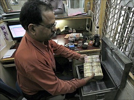 An employee arranges Indian currency notes at a cash counter inside a bank in New Delhi.