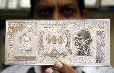 A jeweller displays a silver plate in the form of an Indian rupee note.