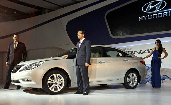 Arvind Saxena (L), director for sales and marketing at Hyundai India, Park Han Woo (C), managing director of Hyundai India, and a model pose with the company's new Sonata car after its launch at India's Auto Expo in New Delhi.