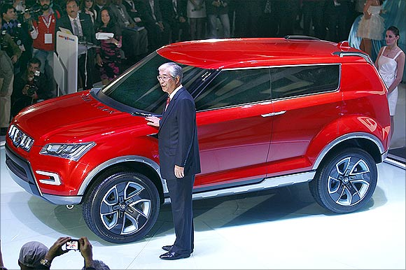 Shinzo Nakanishi, chief executive and managing director of Maruti Suzuki, poses with company's new compact SUV XA Alpha car.