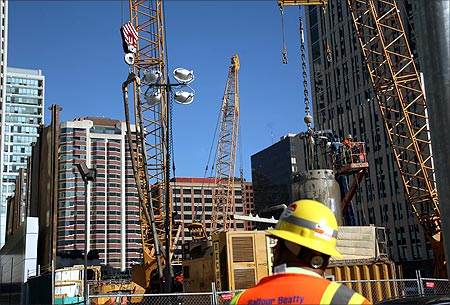 A worker stands in front of a construction site in San Francisco.