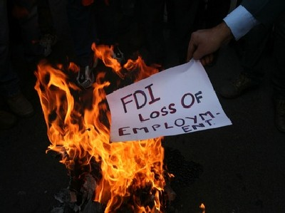 An activist of Shiv Sena burns a pamphlet during a protest against Foreign Direct Investment.