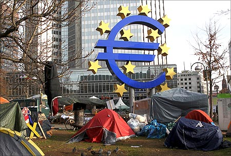 Tents of the 'Occupy Frankfurt' movement are pictured next to the Euro currency sign sculpture in front of the European Central Bank.