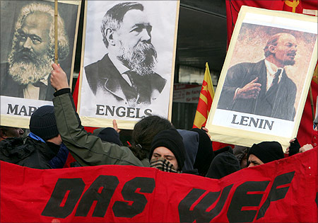 Protesters march in the streets with portraits of Karl Marx, Friederich Engels and Vladimir Lenin during a demonstration.