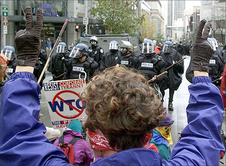 A woman raises her hands in a peace sign as riot police take back control of a downtown intersection in Seattle.