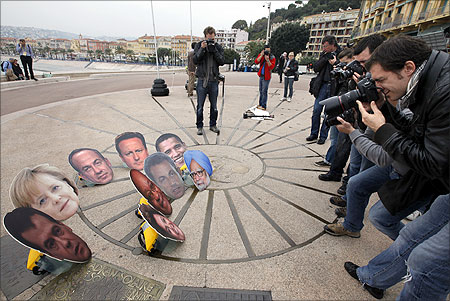 Photographers take photo of masks showing G20 leaders during an anti G20 demonstration to protest against globalisation in Nice ahead of the G20 summit.