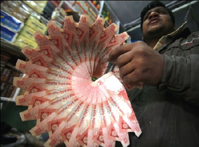 A shopkeeper holds a garland made of Rs 20 notes.