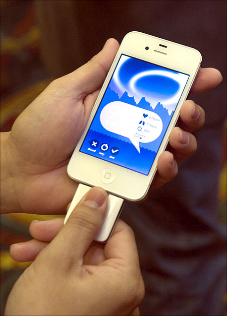 A woman tries out a Tinke device by Zensorium on an iPhone.